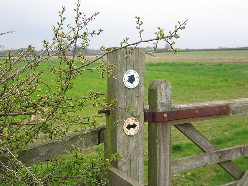 Gate post in field with footpath and bridleway notices